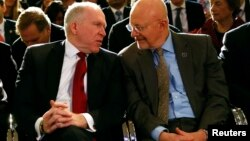 FILE - Then CIA Director John Brennan (L) speaks to then Director of National Intelligence James Clapper at the Justice Department in Washington, Jan. 17, 2014. Both Brennan and Trump had harsh words Friday for President Donald Trump at the Aspen Security Forum in Colorado.