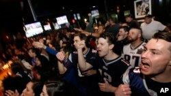 Coleman Hands, center, of Dallas, Davis Smith, second from right, of Austin, Texas, and Brian Moran, right, of Boston cheer while watching the first half of the NFL Super Bowl 52 football game between the New England Patriots and the Philadelphia Eagles in Minneapolis, Sunday, Feb. 4, 2018.