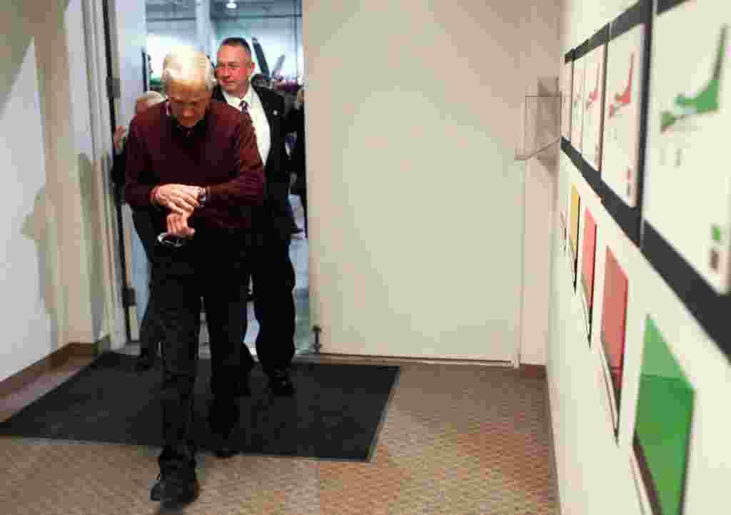 Ron Paul mengecek jam tangannya saat mengunjungi markas perusahaan pesawat terbang Quest di Sandpoint, Idaho, 5 Maret 2012 (AP).