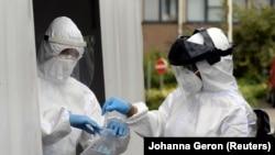 Staf medis menangani sampel di tempat pengujian drive-in untuk penyakit coronavirus (COVID-19) di sebuah rumah sakit di Brussel, Belgia 27 Juli 2020. (REUTERS / Johanna Geron)