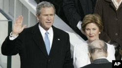 President George W. Bush takes the oath of office for his second term with his wife Laura Bush at his side