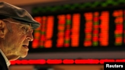 FILE - A Brazilian investor looks at the stock price monitors at the BM&FBOVESPA Stock Market in Sao Paulo, Aug. 10, 2011.