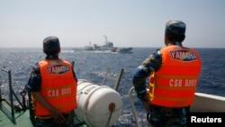 资料照:越南海岸警卫队成员在南中国海海域注视着一艘中国海警船只。