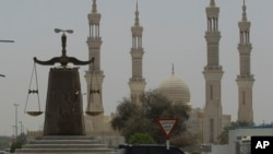 FILE - A justice symbol monument in front of a mosque in Ras al Khaimah, United Arab Emirates, July 2, 2013.