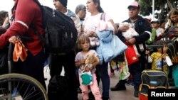 Manm karavàn imigran ki sòti nan Amerik Santral la ap tann pou yo travèse fwontyè amerikano-meksiken an kote yo espere otorite Sèvis Fwontyè ak Ladwann Lèzetazini va kite yo aplike pou azil. (Tijuana, Meksik, 29 avril 2018. Foto: REUTERS/Edgard Garrido).