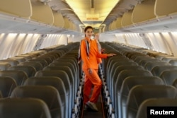 Flight attendants of SkyUp Airlines pose for a picture onboard a plane during the presentation of a new uniform at the Boryspil International Airport outside Kyiv, Ukraine September 30, 2021. (REUTERS/Gleb Garanich)