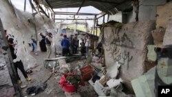 Warga setempat memeriksa lokasi pasca serangan bom bunuh diri di pasar yang ramai di kota Sadr, Irak, 2 Januari 2016. (AP Photo/ Karim Kadim).