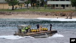 FILE - A group of Vietnamese asylum seekers are taken by barge to a jetty on Australia's Christmas Island. Australian officials said police regained control of the center after negotiating with the inmates, but added it had to use 'some force' with a group of detainees who had barricaded themselves and threatened to use weapons.