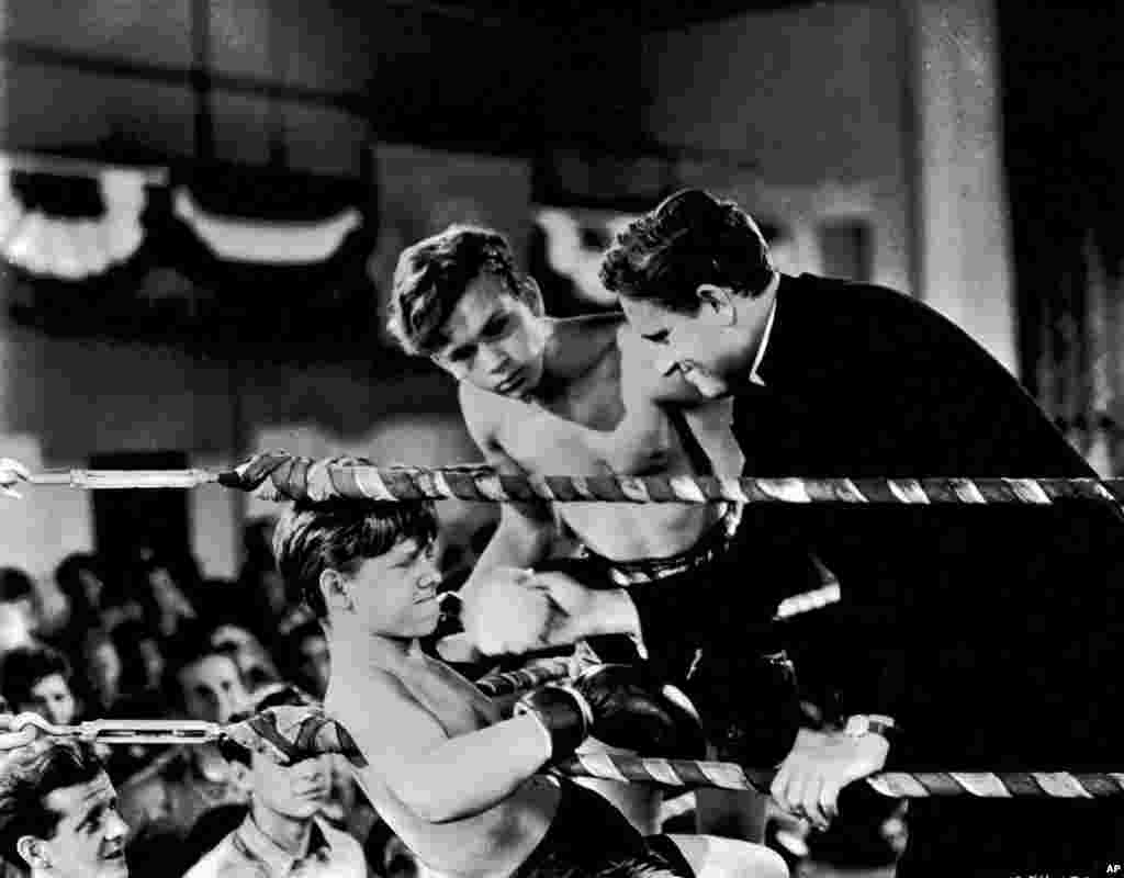 "Mickey Rooney is against the ropes as Spencer Tracy stands by him in this scene from the 1938 movie ""Boys Town."""