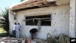 一名以色列男子檢查受襲擊房屋。