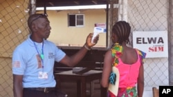 Seorang petugas kesehatan memeriksa temperatur seorang perempuan yang anggota keluarganya dites positif ebola pada sebuah klinik di Monrovia, Liberia (20/11).