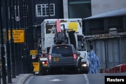 FILE - Forensics investigators work as a white van is carried away from London Bridge, after attackers rammed a hired van into pedestrians on London Bridge and stabbed others nearby killing and injuring people, in London, Britain, June 4, 2017.