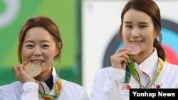 한국 여자양궁 대표팀의 장혜진(왼쪽)과 기보배가 11일 브라질 리우올림픽 양궁 여자 개인전에서 각각 금메달과 동메달을 따낸 뒤 시상식에서 포즈를 취하고 있다.