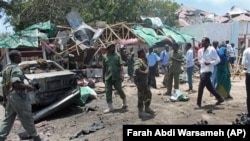 Somali soldiers gather near the destroyed restaurant in Mogadishu, Somalia, Saturday, Sept, 7, 2013. Police in Somalia say two explosions against a restaurant frequented by government workers has killed at least 15 people. Early reports indicated that a c