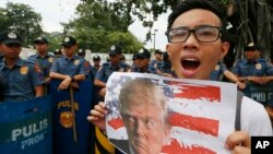 Polisi Filipina berjaga-jaga di depan Kedutaan Besar AS di Manila, di tengah demonstrasi anti-Trump (10/11). (AP/Bullit Marquez)