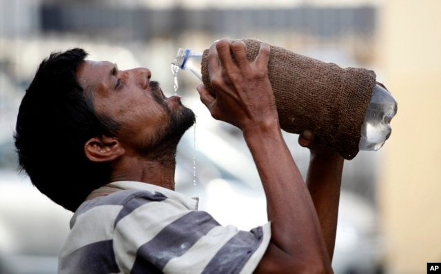 FILE - An Indian drinks water from a bottle on a hot summer day in Allahabad, India.