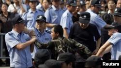 警方人員星期六在浙江省寧波市逮捕抗議計劃擴建化工廠的示威者