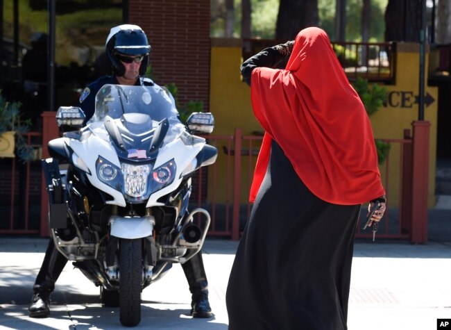 FILE - A Muslim woman leaves a protest as a San Diego police officer looks on after protesters marched through El Cajon, Calif., Oct. 1, 2016, in reaction to Alfred Olango's death.