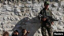 Seorang anggota pasukan keamanan Afghanistan mengawasi para militan ISIS yang menyerah kepada pemerintah, sementara anak-anak dari keluarga militan berada di dekatnya, di distrik Achin, provinsi Nangarhar, Afghanistan (17/11).