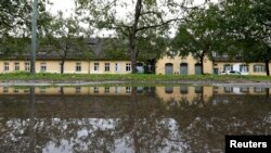 An annex of the former Nazi concentration camp Dachau, which has been turned into a shelter for homeless, including refugees, is reflected in a puddle in Dachau, Germany, Sept. 23, 2015.