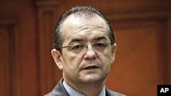 Romanian Premier Emil Boc looks at lawmakers before a no-confidence vote in Bucharest, Romania. Premier Emil Boc announced the immediate resignation of himself and his government on Monday, February 6, 2012, saying he wanted to protect the stability of th