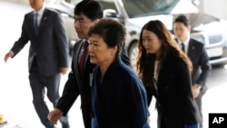 "South Korea's ousted leader Park Geun-hye, foreground, arrives at a prosecutor's office in Seoul, South Korea, March 21, 2017. Park said she was ""sorry"" to the people as she arrived Tuesday at a prosecutors' office for questioning over a corruption scandal that led to her removal from office."