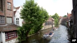 FILE - Tourists ride in a boat down a main canal in Bruges, Belgium, May 26, 2016. Tourism has dropped in Belgium since the deadly bombings in March.