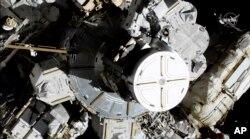 En esta foto provista por la NASA las astronautas Christina Koch y Jessica Meir salen de la estación espacial internacional el viernes, 18 de octubre, de 2019.