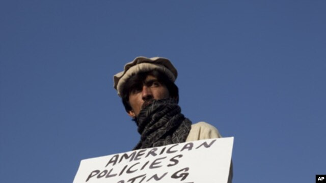 A Pakistani tribesman from North Waziristan tribal region holds a placard during a protest against U.S. drone strikes near the parliament house in Islamabad on 10,  Dec 2010.