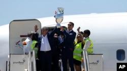 Cristiano Ronaldo et le coach Fernando Santos, (gauche), présentant, après leur victoire sur la France en finale, le trophée de l'Euro 2016 à l'aéroport Humberto Delgado de Lisbon, Portugal, lundi 11 juillet, 2016. (AP Photo/Paulo Duarte)
