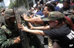 FILE - Protesters push Thai soldiers with shields during an anti-coup demonstration in Bangkok, Thailand, May 25, 2014.