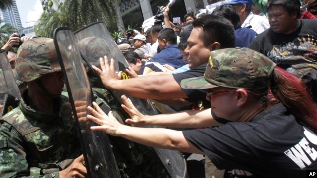 Protesters push Thai soldiers with shields during an anti-coup demonstration in Bangkok, Thailand, May 25, 2014.