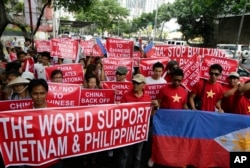 """越南人和菲律宾人在中国驻菲律宾领事馆前示威,标语牌上写着""""对中国人说不"""",""""世界支持越南和菲律宾"""""""