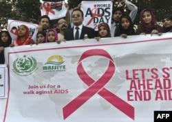 ນັກເຄື່ອນໄຫວປາກິສຖານ ຖືປ້າຍສັນຍາລັກ ວັນ AIDS ໃນນະຄອນລາຮໍ ວັນທີ 1 ທັນວາ 2016.
