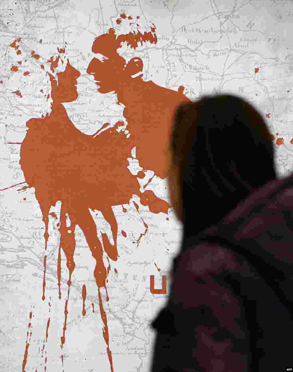 """Devojka prolazi pored postera za film """"U zemlji krvi i meda"""" Anđeline Džoli, u Beogradu, 24. februara 2012. (AP)"""