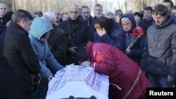 5일 러시아 상테페테르부르크에서 열린 여객기 추락 사고 희생자 장례식에서 유가족이 관을 잡고 오열하고 있다.