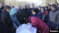 Relatives mourn next to a coffin of Alexei Alexeev, a victim of a Russian airliner which crashed in Egypt, during a funeral ceremony at the Bogoslovskoye cemetery in St. Petersburg, Russia, Nov. 5, 2015.