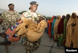 FILE - Major General Rogers Nicholas carries one of the newly released Dapchi schoolgirls as others wait to board a plane in Maiduguri, Nigeria, March 21, 2018.