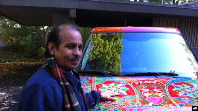 Pakistani truck and bus artist Ghulam Sarwar stands in front of a car he recently painted.