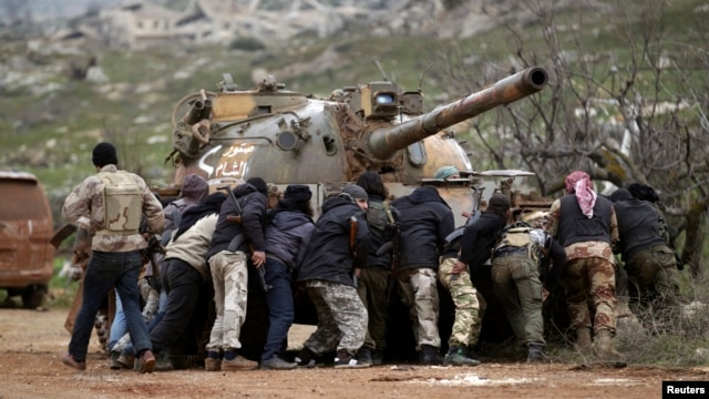 FILE - Fighters from the Suqour al-Sham Brigade, which is part of the Free Syrian Army, take cover from snipers during what activists said were clashes with forces of Syria's President Bashar al-Assad, in the al-Arbaeen mountain area of western Idlib, Jan. 30, 2015.