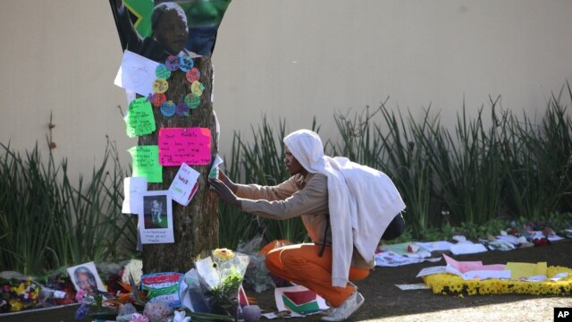 A man takes a moment to read some of the get well wishes and messages outside Nelson Mandela's house in Johannesburg, South Africa, July, 4, 2013.
