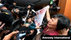 "A Chinese relative of passengers aboard a missing Malaysia Airlines plane cries as she holds a banner in front of journalists reading 'We are against the Malaysian government for hiding the truth and delaying the rescue. Release our families unconditionally!"" at a hotel in Sepang, Malaysia, Mar. 19, 2014."