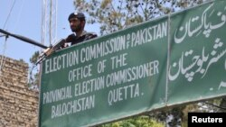 FILE - A policeman stands guard at an election commission office in Quetta, May 8, 2013. Pakistan's Election Commission has again rejected the registration of Milli Muslim League, citing its alleged terror ties. General elections are scheduled for July 25.
