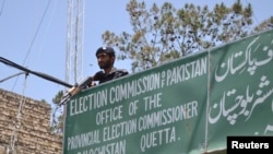 FILE - A policeman stands guard at an Election Commission office in Quetta, Pakistan, May 8, 2013. The Election Commission has twice rejected the registration of Milli Muslim League, citing its alleged terror ties. General elections are scheduled for July 25.
