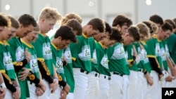 Santa Fe High School baseball players bow their heads in a moment of silence for the shooting victims at their school before a baseball game against Kingwood Park High School in Deer Park, Texas, May 19, 2018. Another moment of silence was observed Monday throughout Texas.