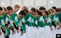 Jugadores de béisbol de la secundaria Santa Fe, observan un momento de silencio en honor de las víctimas de un tiroteo en su escuela. Mayo 19, 2018.