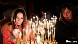 在乌克兰总统亚努科维奇被示威运动推翻后,人们在基辅的一座教堂举行的宗教仪式上点燃蜡烛。(2014年2月23日)