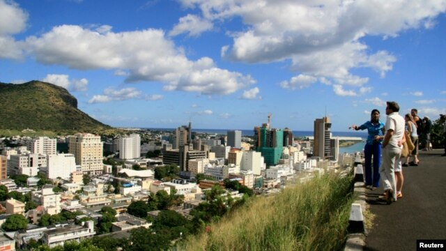 FILE - A tour guide stands with a group of tourists at a viewpoint overlooking Port Louis on June 6, 2008. Mauritius took the top spot once again in annual index.