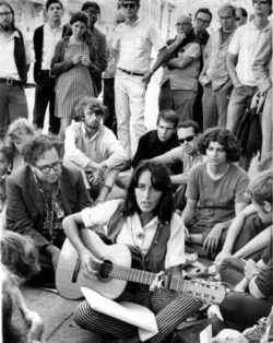 """Folk singer Joan Baez sits at the corner of Haight and Ashbury streets in San Francisco in September 1967during the """"Summer of Love"""""""