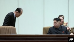 ທ່ານ Kim Yong Nam (ຊ້າຍ) ປະທານບໍລິຫານສູງສຸດ ຂອງສະພາປະຊາຊົນສູງສຸດຂອງເກົາຫລີເໜືອ ກົ້ມຫົວຄໍານັບ ທ່ານ Kim Jong Un, ຜູ້ນໍາເກົາຫລີເໜືອ ໃນກອງປະຊຸມເຈົ້າໜ້າທີ່ຂັ້ນສູງຂອງພັກ ແລະກອງທັລເກົາຫລີເໜືອ ໃນວັນທີ 16 ທັນວາ 2012.